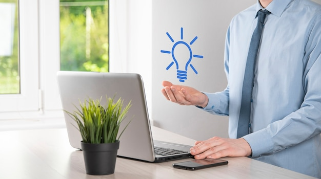 손을 잡고 전구. 고립 된 스마트 아이디어 아이콘입니다. 혁신, 솔루션 아이콘. 에너지 솔루션. 파워 아이디어 개념. 전기 램프, 기술 발명. 인간의 손바닥. 비즈니스 영감. 프리미엄 사진