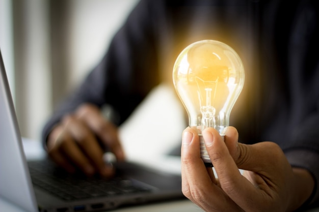 Hand holding light bulb with a laptop in the background