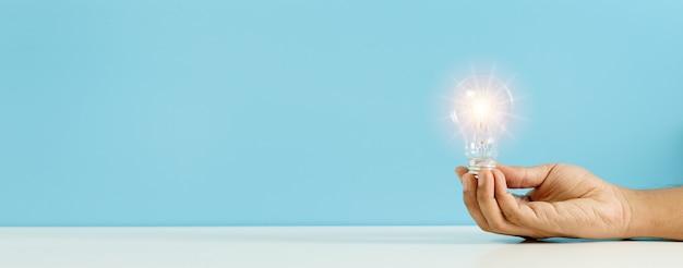 밝은 플레어 파란색 배경으로 전구를 들고 손입니다. 창의성, 아이디어 및 창의적인 개념의 상징입니다. 공간 배너를 복사합니다.