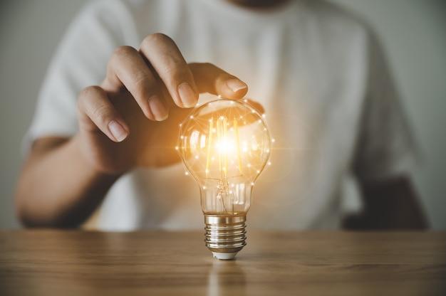 Hand holding light bulb on wood table