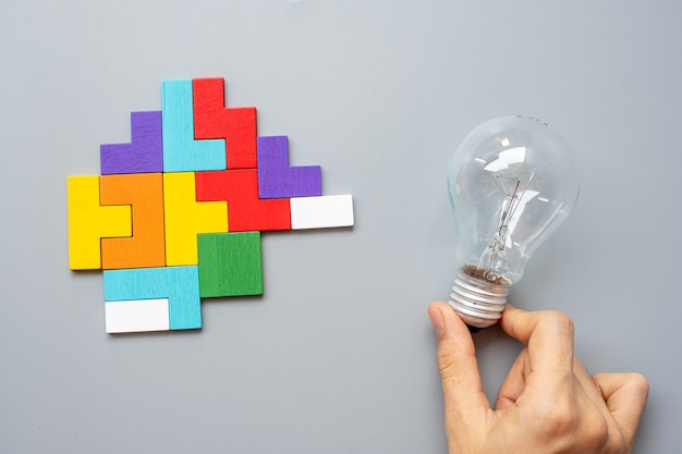 Hand holding lightbulb with colorful wood puzzle piece on gray . new idea, creative, innovation, imagination, inspiration, solution, strategy and logic concept