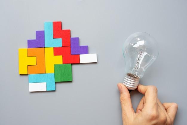 회색에 다채로운 나무 퍼즐 조각으로 전구를 들고 손. 새로운 아이디어, 창의적, 혁신, 상상력, 영감, 솔루션, 전략 및 논리 개념
