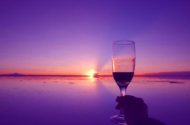 ボリビアのウユニ塩原の氾濫する塩原に沈む夕日に逆らって酒ガラスを持っている手