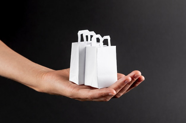 Hand holding little white bags