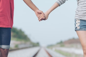 Hand holding Lovers walk on the railway