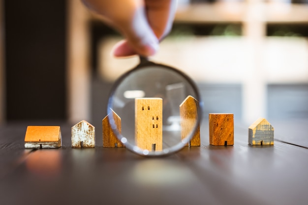 Hand holding magnifying glass and looking at house model,