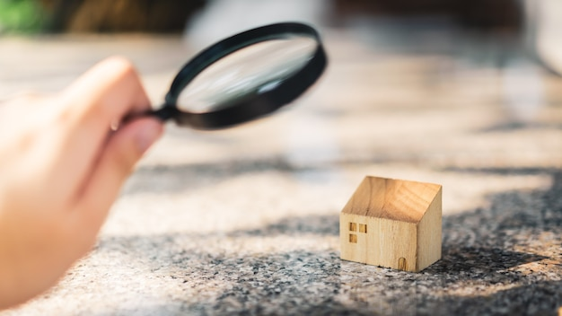 Hand holding magnifying glass and looking at house model