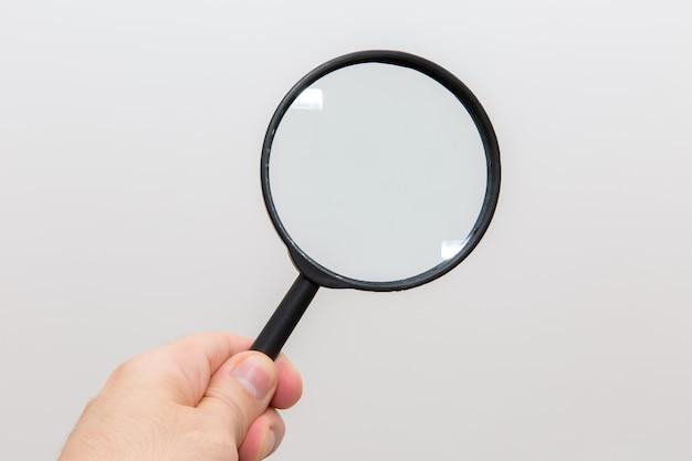 Рука с увеличительным стеклом на белом фоне