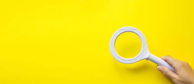 Hand holding magnifying glass on yellow. business analytics and statistics.