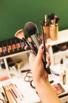 Hand holding make up brushes