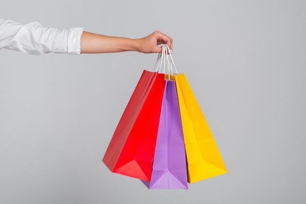 Mano che tiene molte borse della spesa colorate