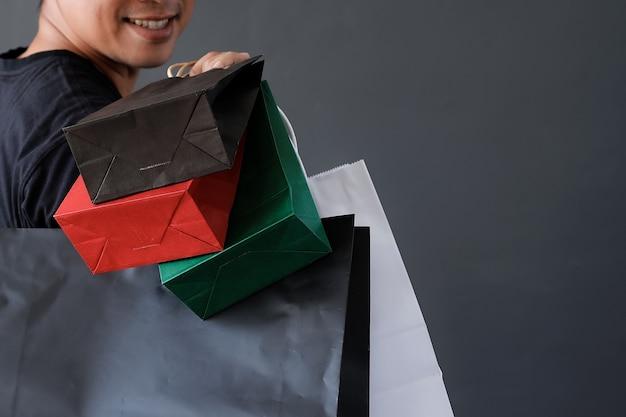 買い物中毒の概念のための多くの買い物袋またはグッディーバッグを持っている手