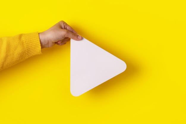 손을 유행 노란색 배경 위에 미디어 플레이어 버튼 아이콘을 잡고