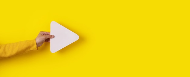 Hand holding media player button icon over trendy yellow background, panoramic layout