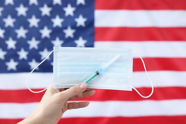 미국 국기 배경 의료 보호 마스크와 주사기를 들고 손