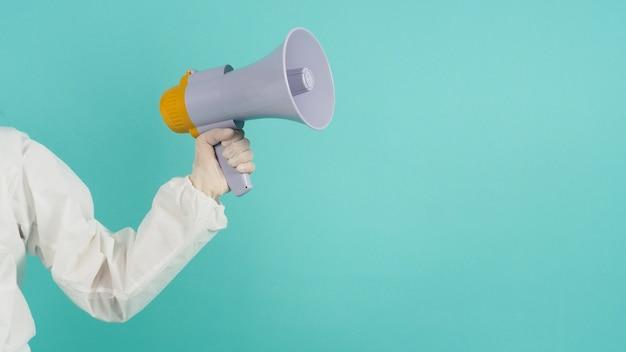 손에 확성기를 들고 ppe 정장, 녹색 민트 또는 tiffany blue 배경에 의료용 장갑을 착용하십시오.