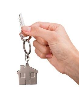 Рука металлический ключ от дома на белом фоне