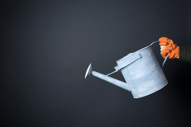 Hand holding metal watering can over grey wall