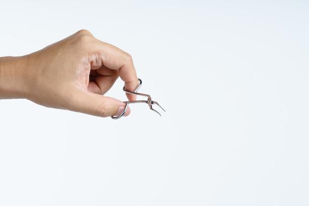 Hand holding metallic tweezers for cosmetic purpose