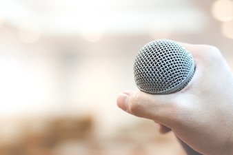 Hand holding microphone on blur background
