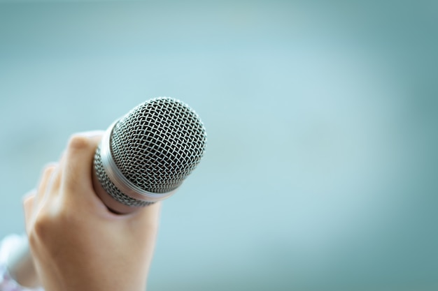 Hand holding microphone on pastel background with copy space