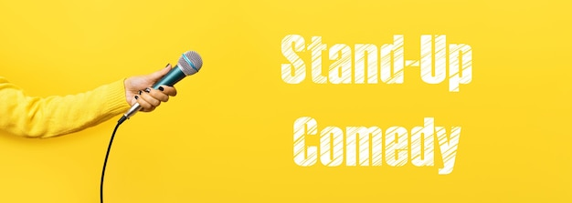 Hand holding microphone over yellow background, panoramic image with stand-up comedy inscription