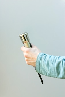 Mano che tiene microfono