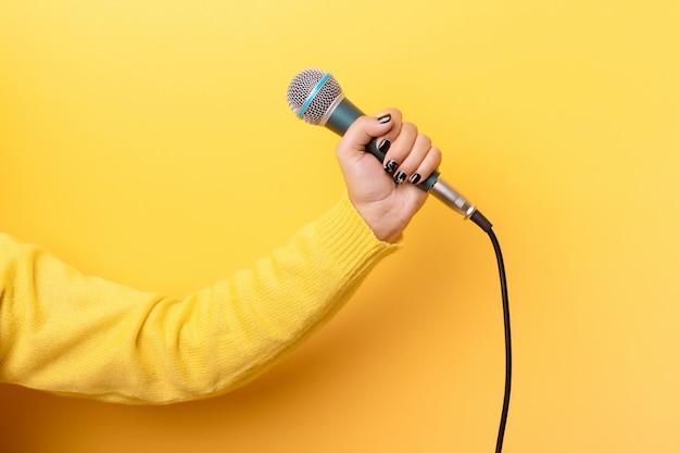 Рука держит микрофон