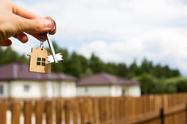 ミニチュアの家と鍵を持っている手