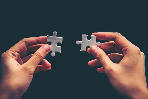Hand holding missing jigsaw puzzle piece down