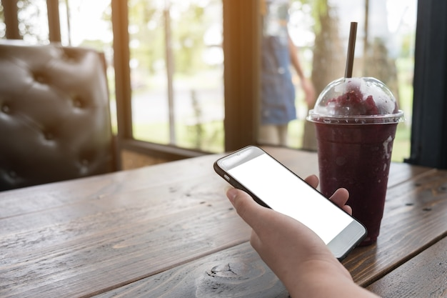 Hand holding mobile phone in coffee shop mock up on screen