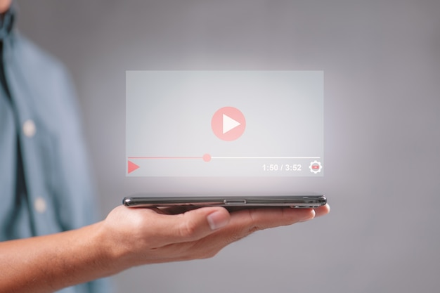 Hand holding mobile phone for live video content online streaming marketing concept.