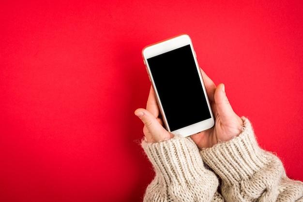 クリスマスのモミの枝と赤で携帯電話を持っている手。