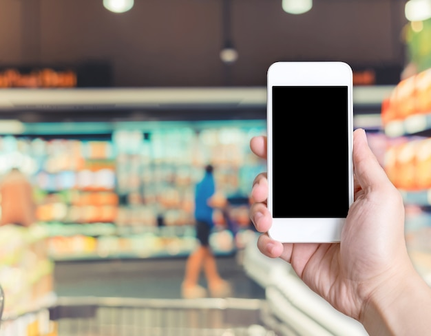 Hand holding mobile phone with blur customer at supermarket store background