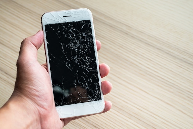 Hand holding mobile phone with broken glass screen