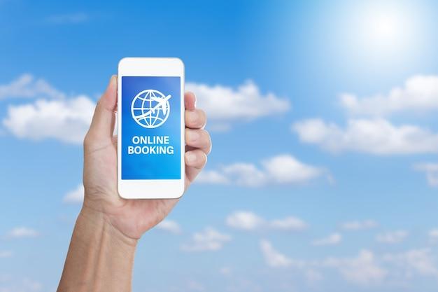 Рука, держащая мобильный телефон со словом онлайн-бронирование на фоне облаков и голубого неба