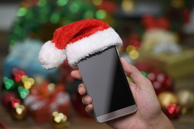 Hand holding mobile phone with santa claus' hat on top on christmas