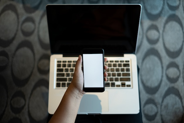 Hand holding a mobile phone with white blank screen over the laptop
