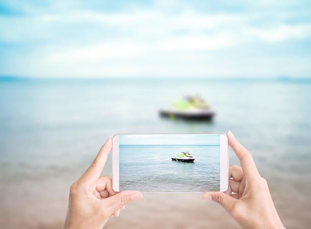 休暇中のぼやけた青い海と青い空の海岸でモバイル写真家の海とスピードボートを持っている手リラックス