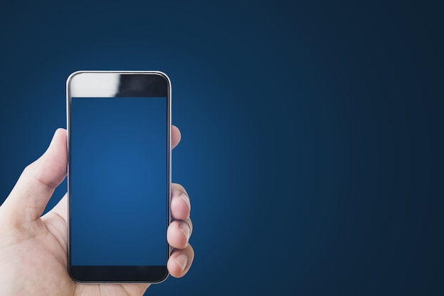 Hand holding mobile smart phone, blank blue screen on gradient blue
