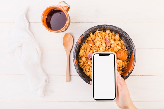 Hand holding mobile on table with dish