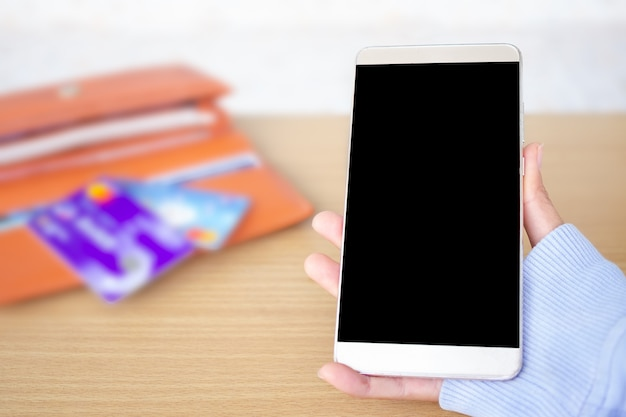 Hand holding mobile with blur image of credit card and billfold. copy space for add text presentation.