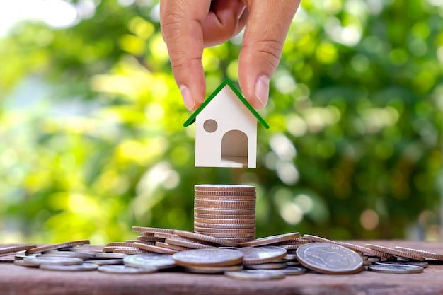 Рука, держащая макет дома на куче монет с размытым зеленым фоном природы, жилищной ссуды и инвестиционной ссуды в недвижимость.
