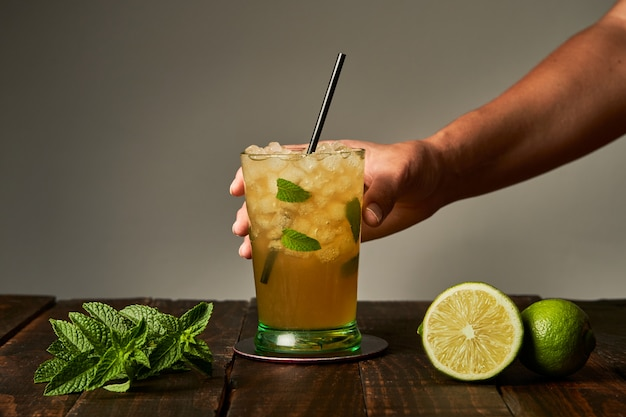 Hand holding a mojito ready to drink at the bar