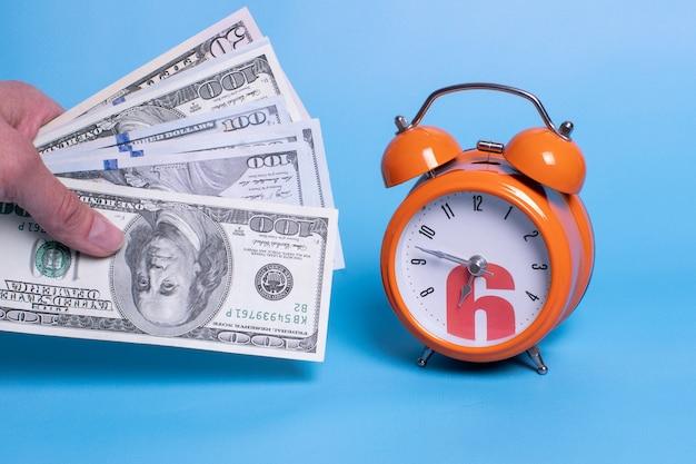 Рука держит деньги рядом с оранжевым будильником