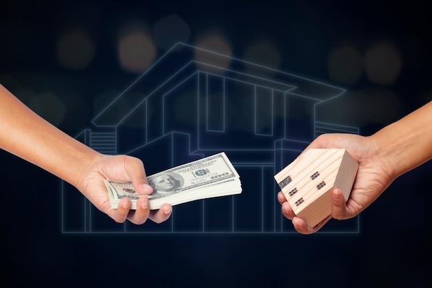 手持ちのお金米ドルと木造モデルハウス。家のコンセプトを売る。