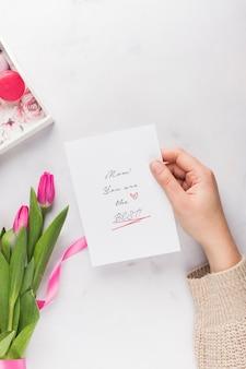 Рука держит карточку дня матери