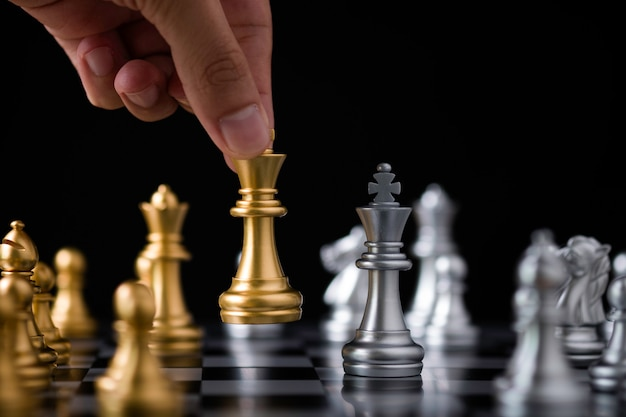 Hand holding and move golden king chess to silver chess.