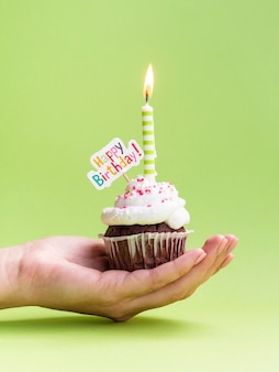 Hand holding muffin with happy birthday sign