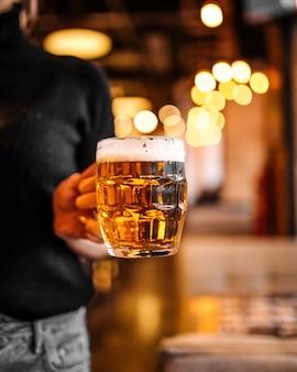 Hand holding mug light beer blurry warm lights